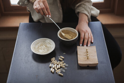 Midsection of woman making herbal medicines at home - CAVF06986