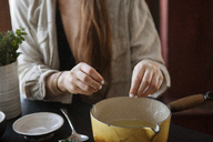 Midsection of young woman making medicines in bowl at home - CAVF06989
