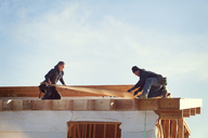 Workers constructing roof beam against sky during sunny day - CAVF07016