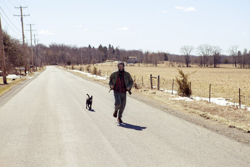 Full length of man and dog running on country road during vacation - CAVF07025