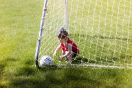 High angle view of girl playing with soccer ball while crouching in goal post on grassy field - CAVF07034