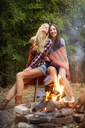 Happy friends sitting on stool by bonfire - CAVF07088