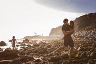 Father carrying daughter while walking on rocks at beach - CAVF07127