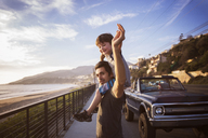 Portrait of father carrying son on shoulders during sunset - CAVF07145