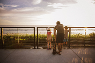 Rear view of family looking at sea while standing by railing during sunset - CAVF07148