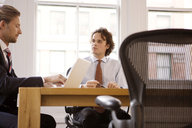 Businessmen sitting at table in office - CAVF07349