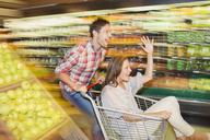Blurred view of couple playing in grocery store - CAIF15581