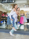 Man carrying girlfriend piggyback in shopping mall - CAIF15584