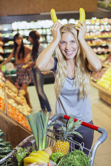Woman playing with bananas while shopping in grocery store - CAIF15587