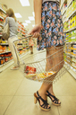 Woman carrying shopping basket in grocery store - CAIF15593