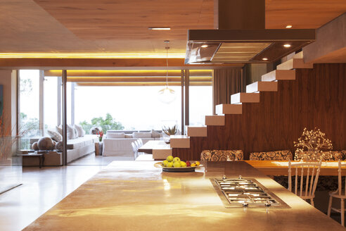 Countertop, staircase, and sofa in open modern kitchen and living area - CAIF15647