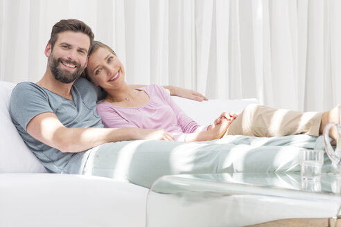 Couple relaxing together on sofa in modern living room - CAIF15674