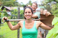 Smiling woman wearing green tank top carrying shovel on shoulders through community garden - CAIF15716