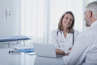 Smiling female doctor talking to patient at desk in office - CAIF15725