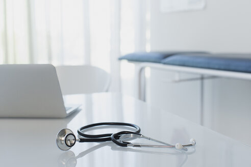 Stethoscope and laptop on white desk in doctors office - CAIF15734