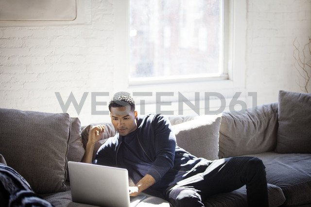 Man using laptop while sitting on sofa at home - CAVF07425 - Cavan Images/Westend61