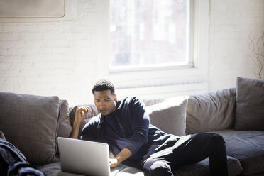 Man using laptop while sitting on sofa at home - CAVF07425