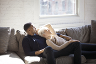 Multi-ethnic couple relaxing on sofa at home - CAVF07428