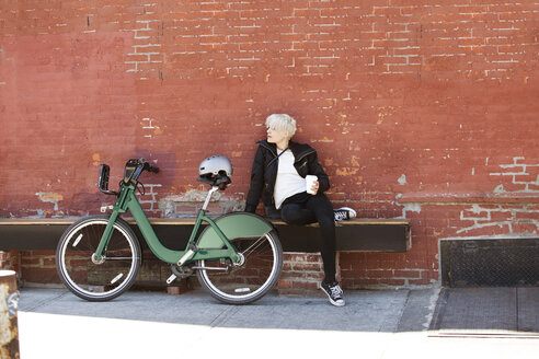 Woman holding coffee while sitting on bench against wall - CAVF07503