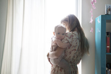 Mother carrying baby while standing by window - CAVF07536