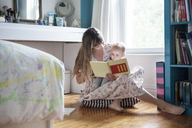 Mother reading book with baby while sitting on floor at home - CAVF07539