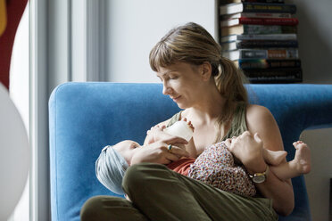 Mother feeding milk to baby with bottle at home - CAVF07545