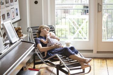 Mother and baby girl sleeping on lounge chair at home - CAVF07557