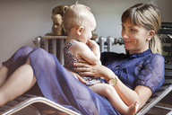 Mother playing with baby while sitting on lounge chair at home - CAVF07560