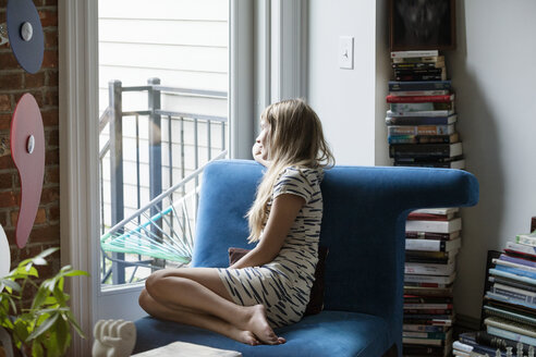 Woman looking through window while sitting on sofa at home - CAVF07572