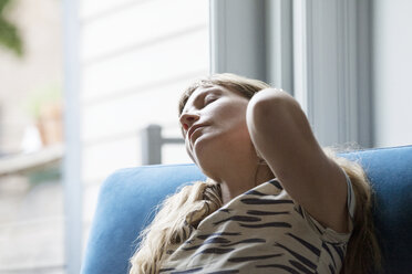 Close-up of tired woman relaxing on sofa - CAVF07575