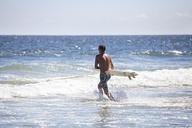 Man carrying surfboard in sea against sky - CAVF07614