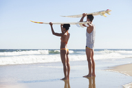 Couple carrying surfboard on head while standing at beach - CAVF07626