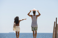 Woman pointing while standing with boyfriend at beach - CAVF07629