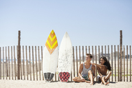 Woman pointing while sitting with boyfriend on sand against fence - CAVF07632
