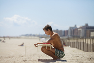Man looking at surfboard while crouching on sand against sky - CAVF07641