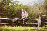 Man looking at saddle while sitting on railing in farm - CAVF07653