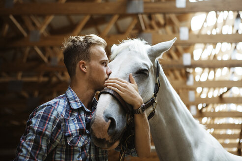 Low angle view of rancher kissing horse in stable - CAVF07668