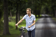 Man looking away while walking with bicycle on road in forest - CAVF07674