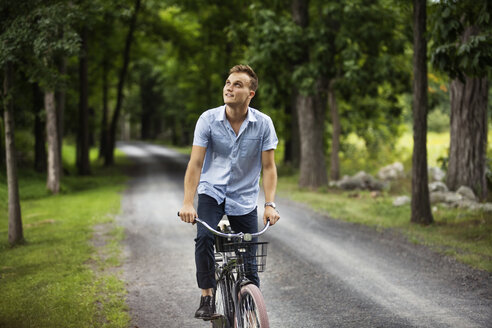 Happy man looking up while riding bicycle on road in woodland - CAVF07677