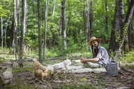 Man looking away while sitting on blanket in forest - CAVF07710