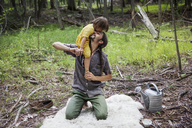 Happy father carrying daughter in forest - CAVF07716