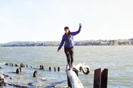 Woman balancing on log over river against clear sky - CAVF07737