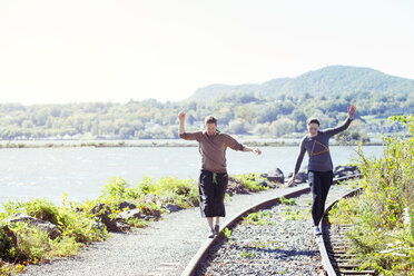 Friends balancing on railroad track against clear sky - CAVF07743
