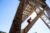 Low angle view of man climbing bridge - CAVF07746
