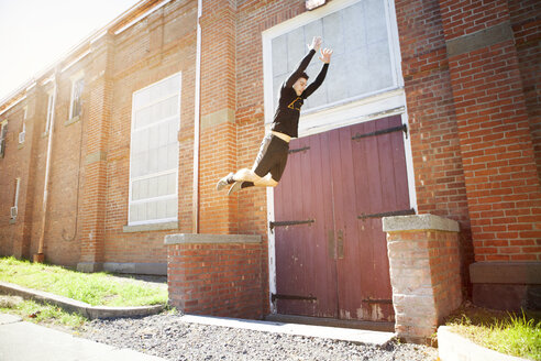 Man jumping by brick wall on sunny day - CAVF07752