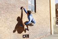Man climbing brick wall - CAVF07755