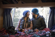 Couple talking while standing by camper van - CAVF07794