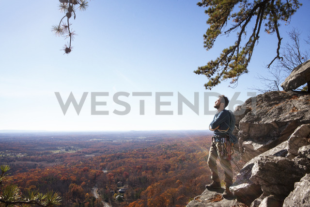 Thoughtful man with arms crossed standing on rocks against sky - CAVF07803