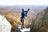 Man holding climbing rope while standing on rock - CAVF07812