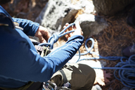 High angle view of man preparing for rock climbing - CAVF07815